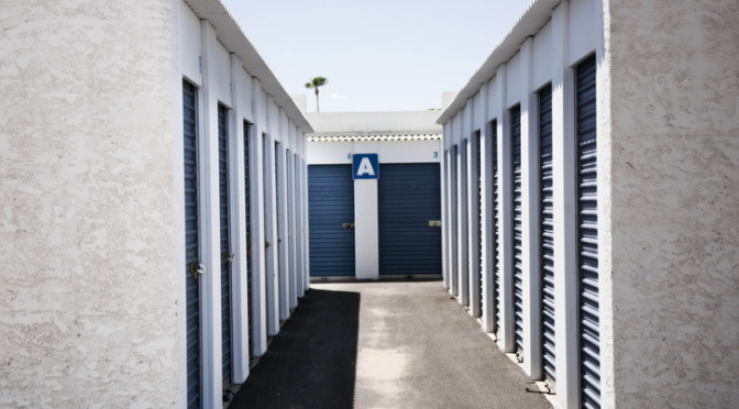 A row of small, outdoor storage units with blue doors in a clean environment
