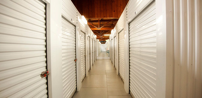A clean, well lit hallway of indoor storage units with white doors