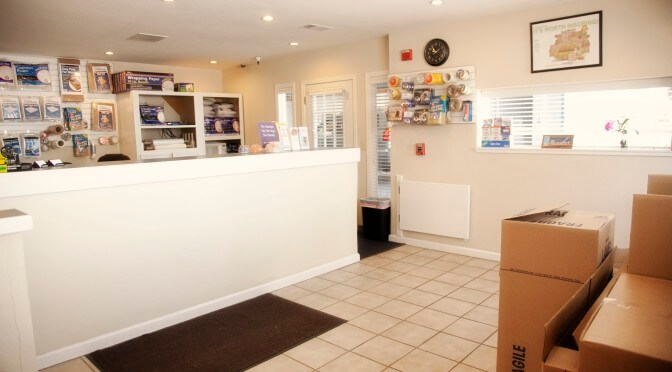 Inside a facility office overlooking the front desk with moving and packing supplies hanging on walls and on shelves