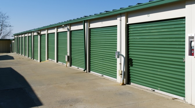 A row of outdoor storage units with green doors in a clean environment