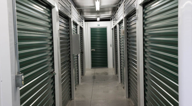 A clean hallway of small indoor storage units with dark green doors