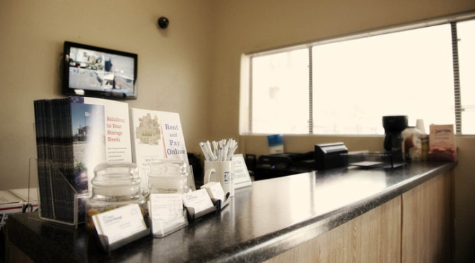 View of facility office overlooking the front desk with a TV monitoring secruity and informational guides