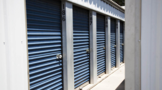 View of small outdoor storage units with blue doors and locks