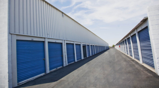 A row of large, outdoor storage units with blue doors in a clean environment