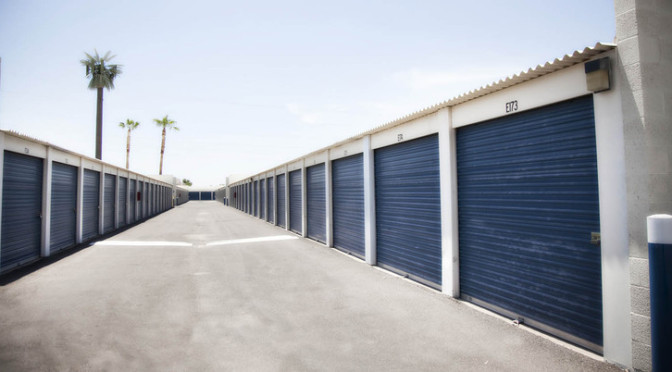 Row of large outdoor storage units with blue doors in a clean environment