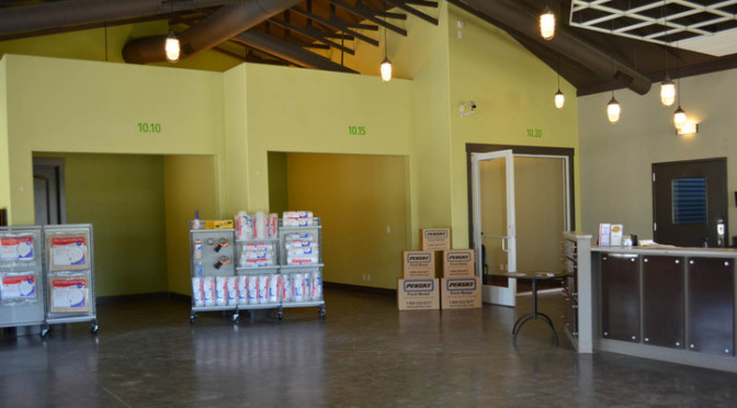An open room with moving and packing supplies available and examples of storage unit sizes