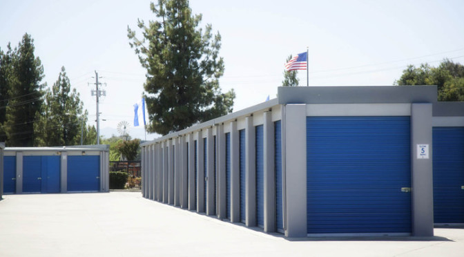Area of large outdoor storage units with blue doors in a clean environment