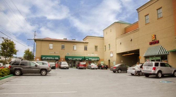 View of a strip mall with a Central Self Storage location entrance