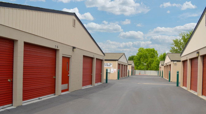 Area of large, outdoor storage units with red doors in a clean environment