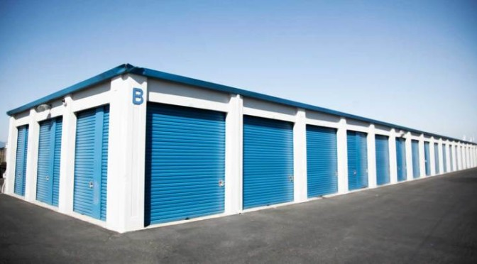 A row of outdoor storage units with blue doors in a clean environment