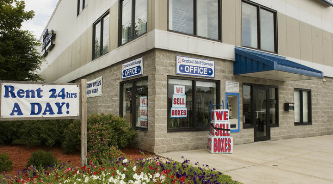 Exterior view of entrance to Central Self Storage office with a promotion for we sell boxes