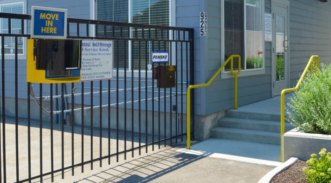 Exterior entrance to a Central Self Storage facility office and a gated entrance