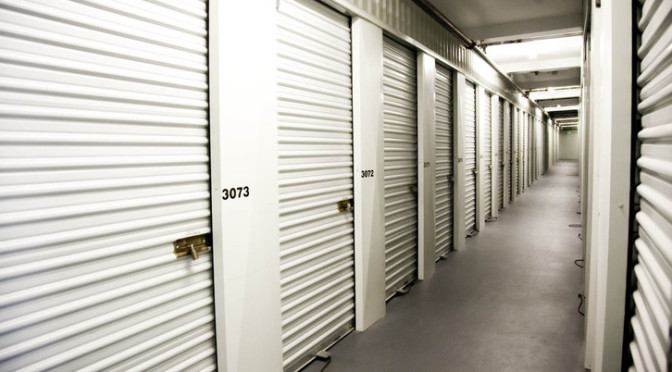 Clean, well lit hallway of indoor storage units with white doors