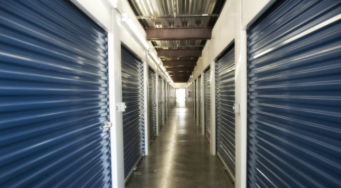 A well lit hallway of indoor storage units with blue doors