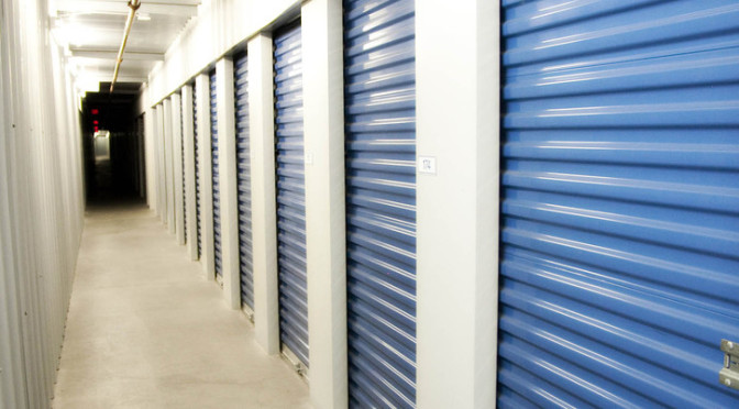 A well lit hallway of small indoor storage units with blue doors