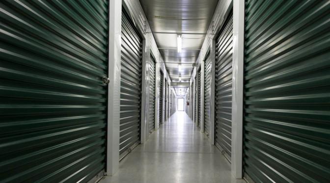 A clean, well lit hallway of indoor storage units with dark green doors