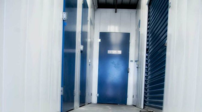 A well lit hallway of small, indoor storage units with blue doors
