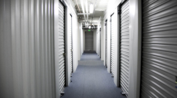 Clean indoor hallway of small storage units with white doors