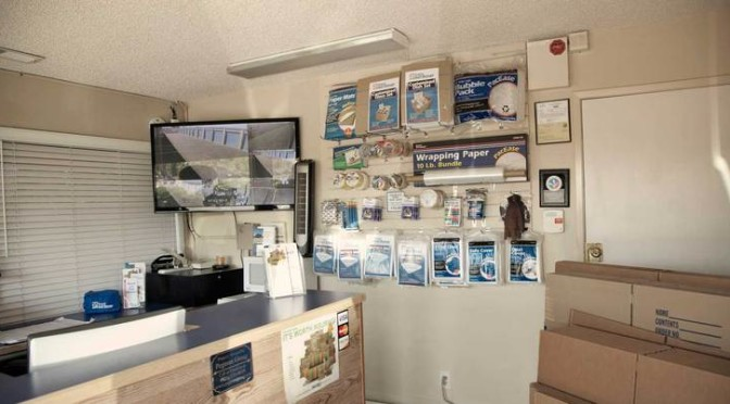 Inside a facility office overlooking the front desk with a TV for security camera footage and moving and packing supplies hanging on wall