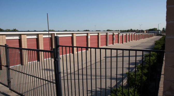 A view of gated entrance to a long row of outdoor storage units with red doors