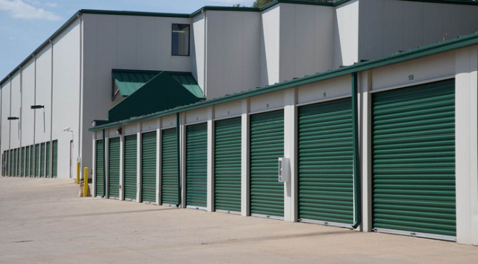 Exterior view of facility with large outdoor storage units with green doors in a clean environment