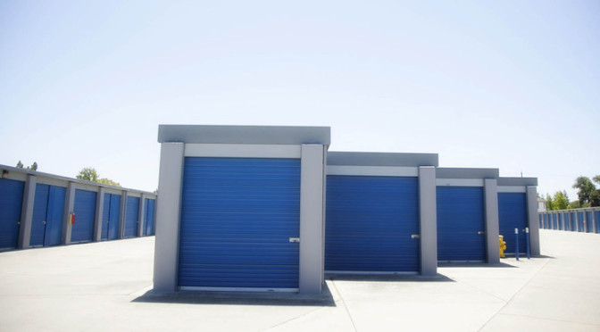 Rows of outdoor storage units with blue doors in a clean environment