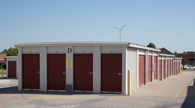 A row of small, outdoor storage units with red doors in a clean environment