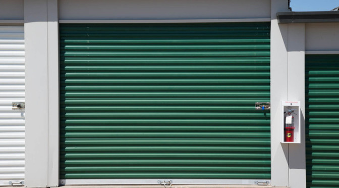 A large, outdoor storage unit with a green door and a secure lock