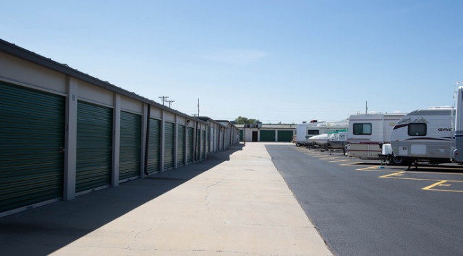 Outdoor area of large outdoor storage units with green doors, and a RV & boat parking lot
