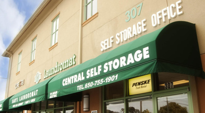 Exterior signage for a Central Self Storage office entrance in a strip mall