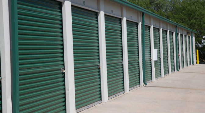 Small outdoor storage units with green doors secured with locks