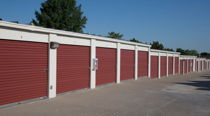 A row of outdoor storage units with red doors in a clean environment