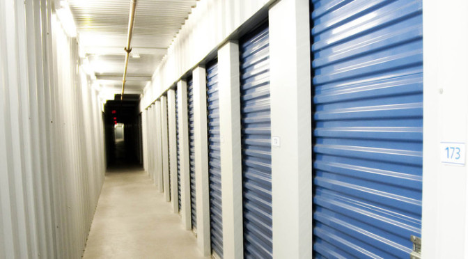 A hallway of small, indoor storage units with blue doors in a clean environment