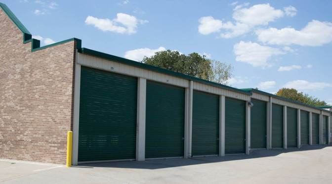 Row of outdoor storage units with green doors in a clean environment