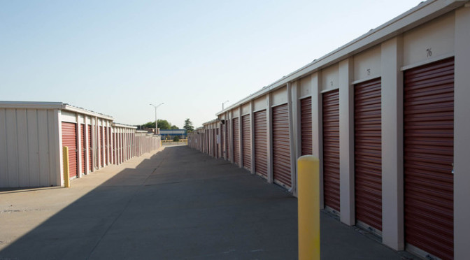 A long row of outdoors storage units with red doors in a clean environment