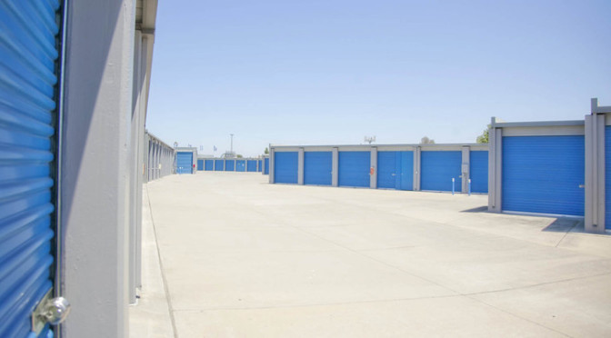 Outdoor area of large storage units with blue doors in a clean environment