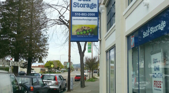 A Central Self Storage facility entrance along the side of a street with a sign hanging above the entrance