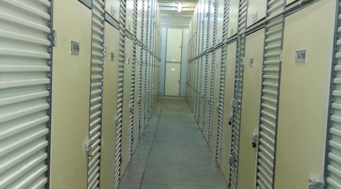A long, well lit hallway of locker storage units with two units lined up vertically