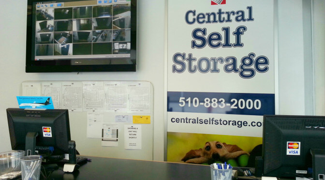 Front desk in Central Self Storage facility office with a TV monitoring security