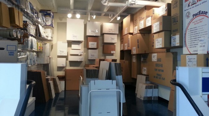 A room with many different box sizes hanging from the wall and around the perimeter of the floor as well as other packing supplies