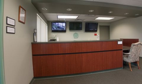 View of facility office overlooking the front desk with TV's monitoring security