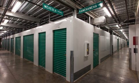 A corner view looking at two hallways that are well lit with indoor storage units