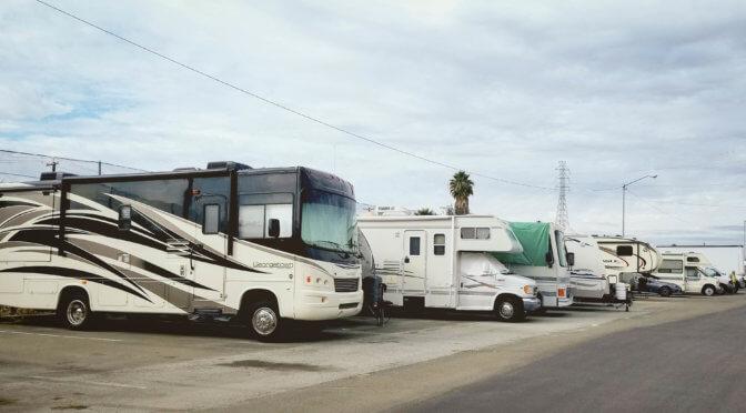 Multiple RV trucks lined up side by side outside in parking lot